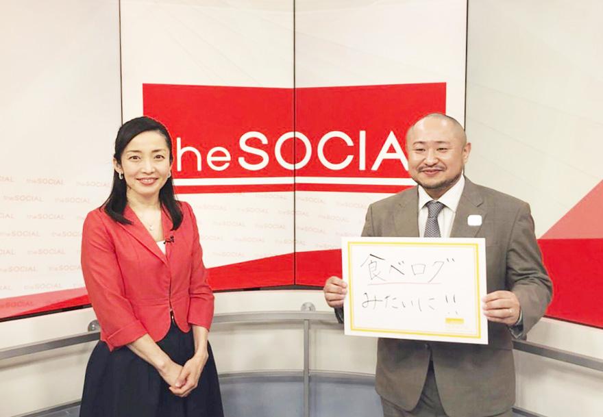 番組スタジオで初瀬勇輔が「食べログみたいに!!」と書かれたフリップを持って、アナウンサーの隣に立っている写真