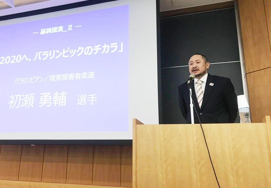 立教大の教室で、スクリーンに映したスライドの前で講演する初瀬勇輔の様子