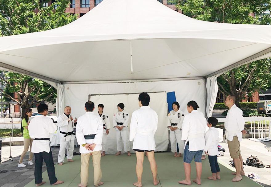 屋外テントに設営された簡易柔道場で、参加者が円になって初瀬勇輔の話を聞いている様子
