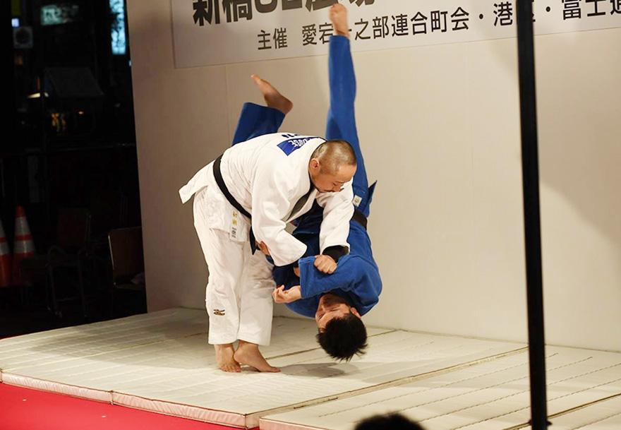 ステージ上のマットで投げ技を披露する初瀬勇輔の写真