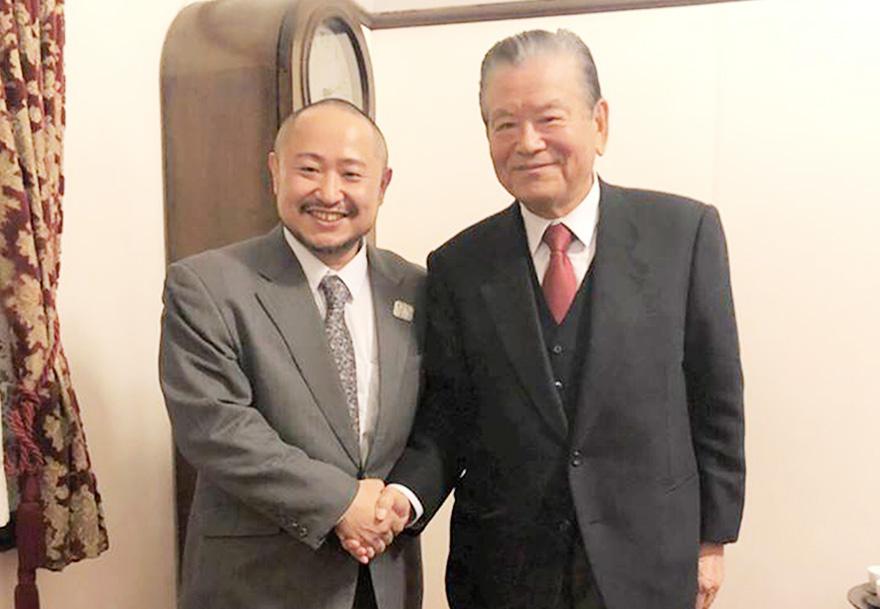 握手をする笑顔の川淵三郎さんと初瀬勇輔の写真