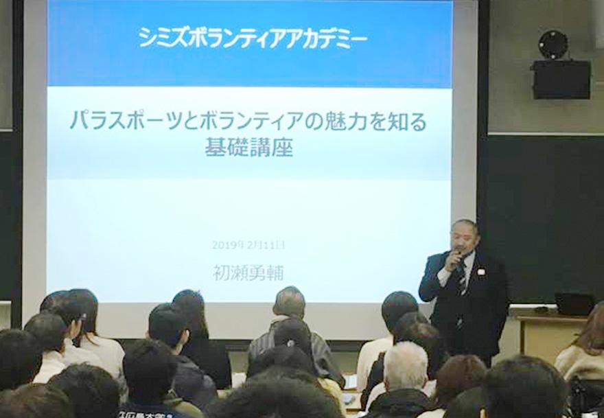 「パラスポーツの魅力を知る基礎講座」と表示されたプロジェクター画面の前で話をする初瀬勇輔