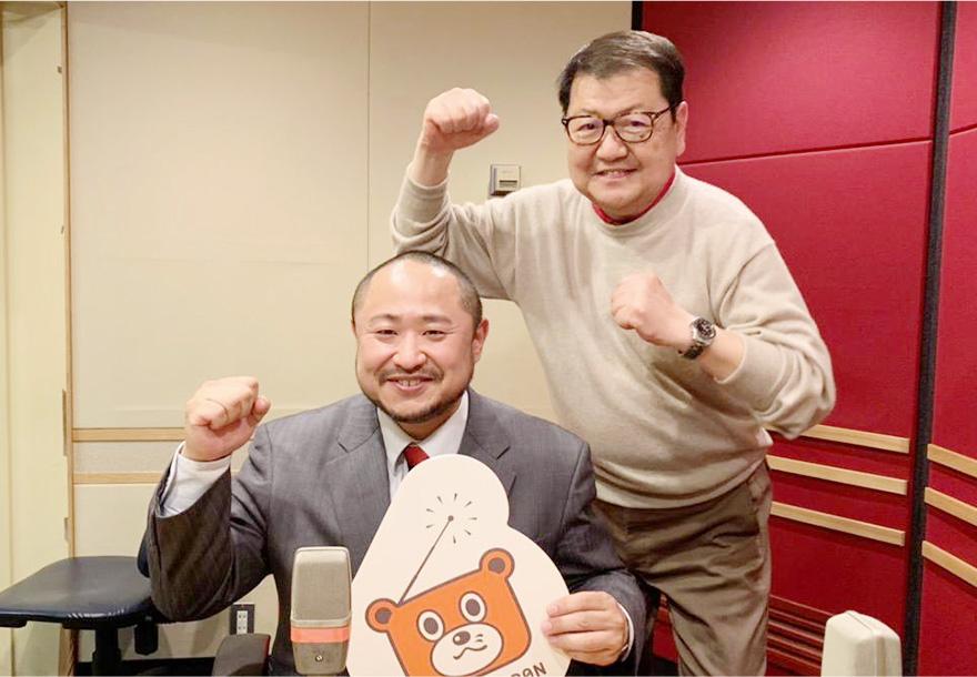ラジオ日本のロゴマークを左手に持ち、右手でガッツポーズをする笑顔の初瀬勇輔