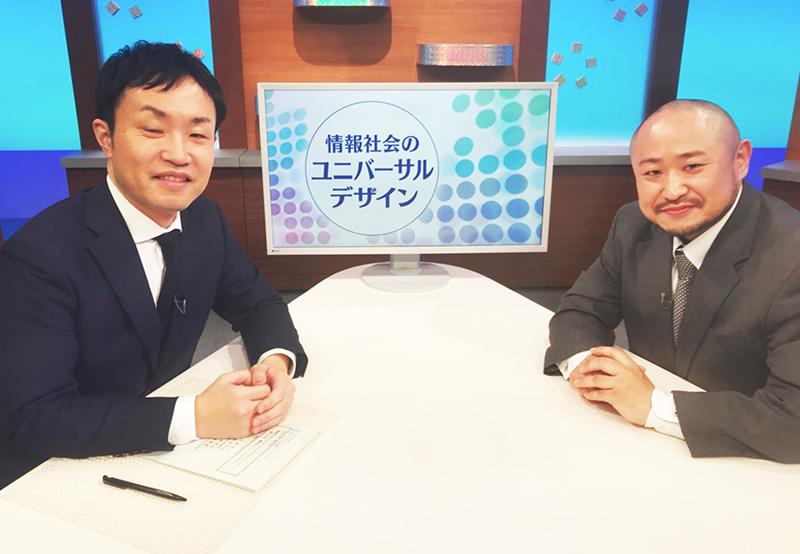 「情報社会のユニバーサルデザイン」と表示されたモニターの前にいる近藤武夫准教授と初瀬勇輔の写真
