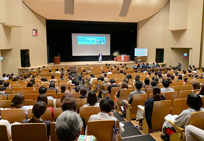 大勢の聴衆を前にステージ上で講演する初瀬の写真