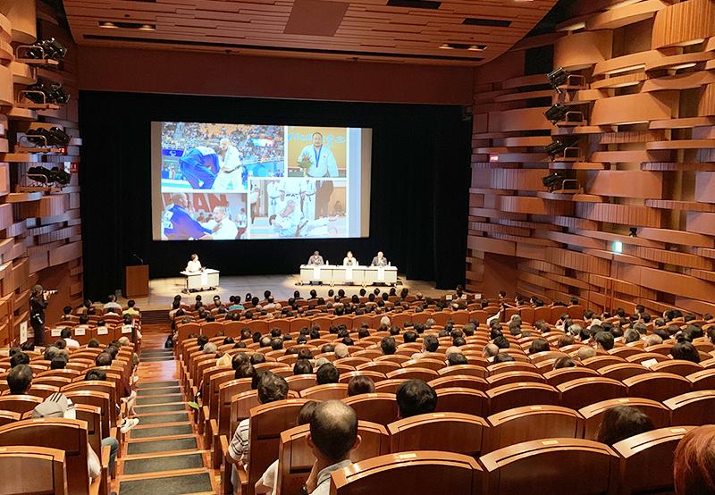 初瀬が障害者柔道アジア大会に出場した時の様子が映し出されたステージ上のプロジェクターを、会場の後方から写した画像