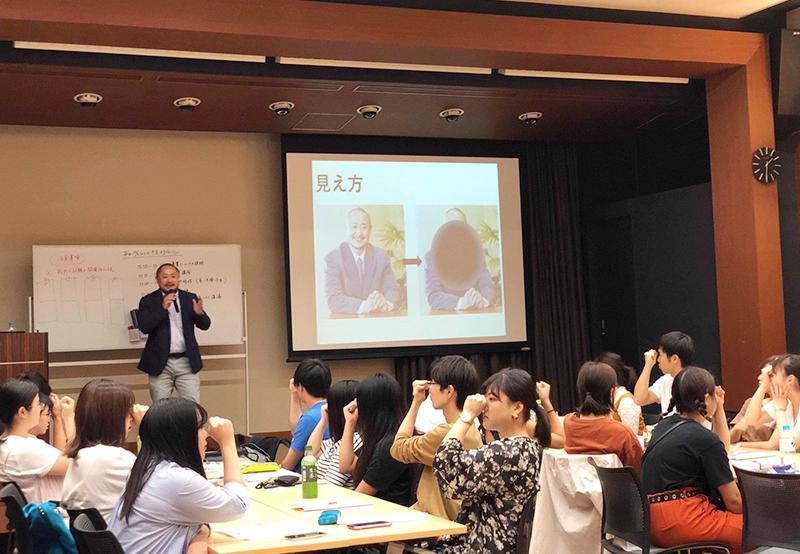 学生ボランティアの方々に自身の視野について説明をする初瀬と、その見え方の擬似体験をしている学生ボランティアの画像