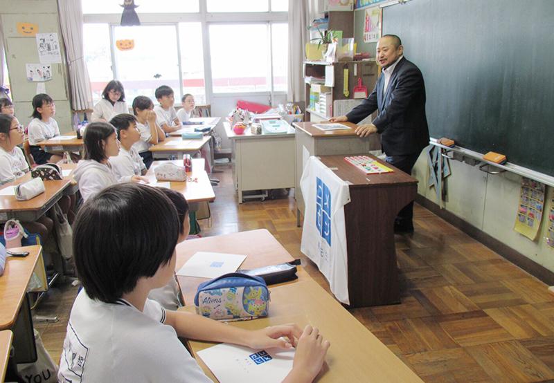 教室の教壇に立ち、子供達に向かって話す初瀬の画像
