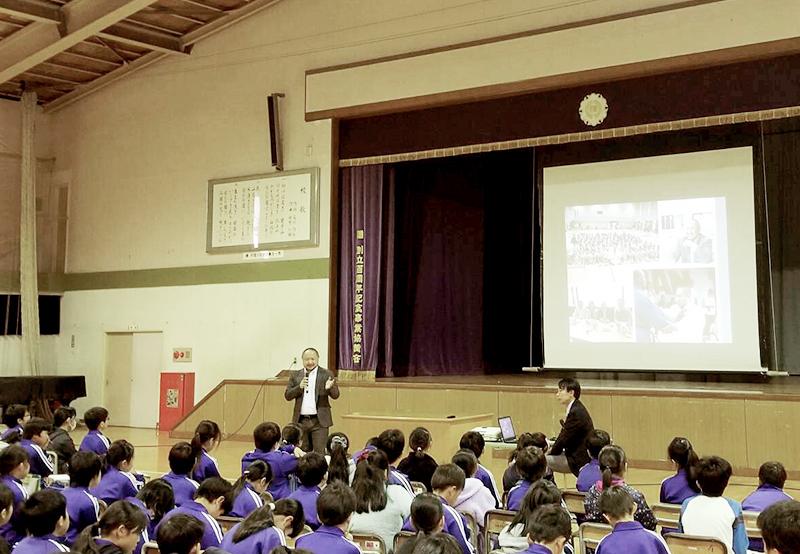 盛岡市仙北小学校の体育館で、ステージ上に設置されたスクリーンに写真を映しながら、子供達に向けて話す初瀬の画像